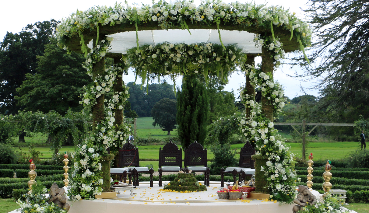 Nishali Moss Mandap with spiral of ENglish styled florals around the pillars and floral border along the top