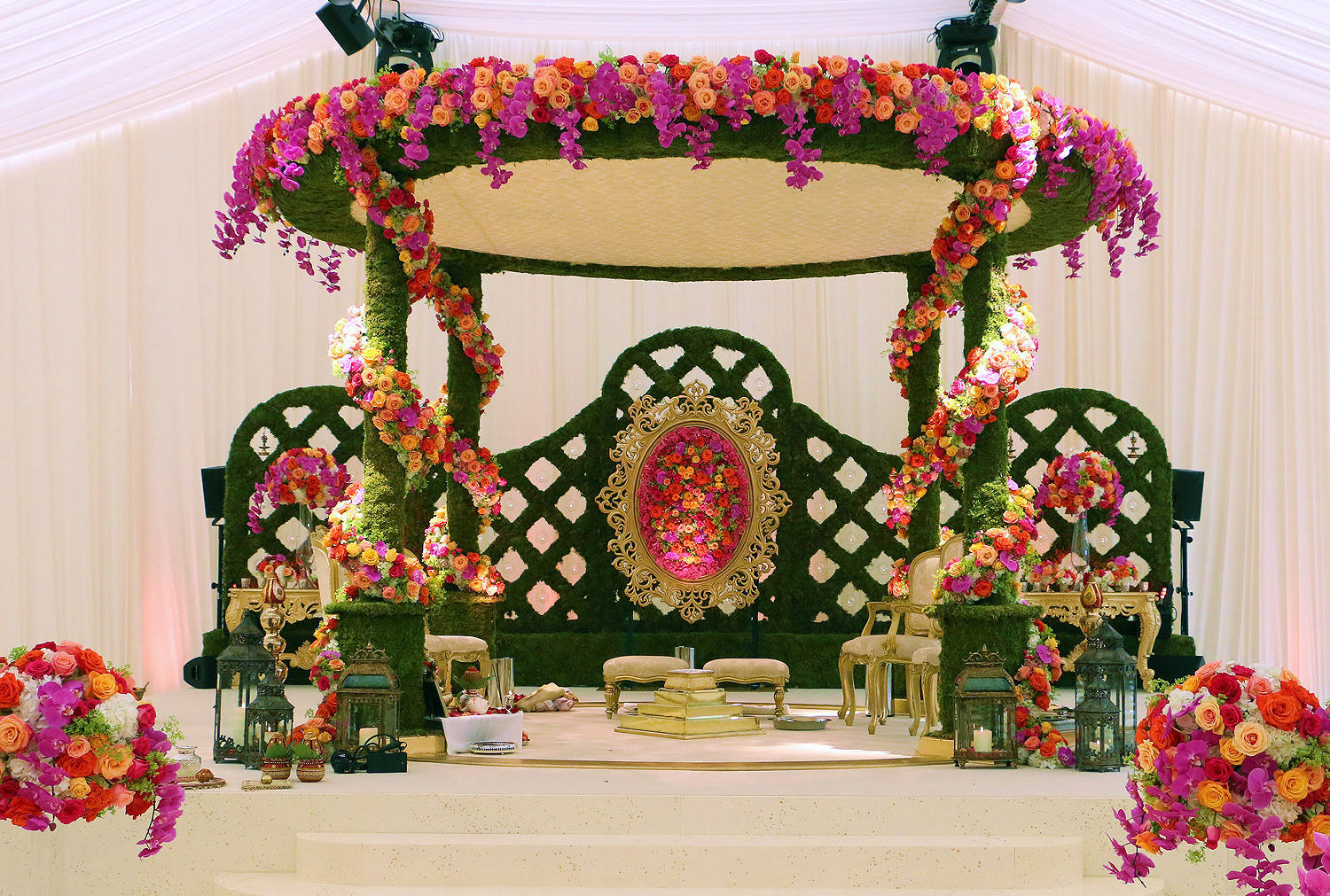 Nishali Floral Mandap. A four pillar Mandap made of moss with moss backdrop and flower filled floral frame