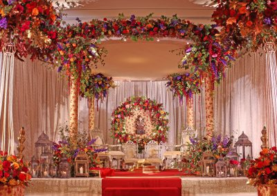 Autumnal Mandap at The Grove. Fabric covered pillars with Halo of flowers in the backdrop