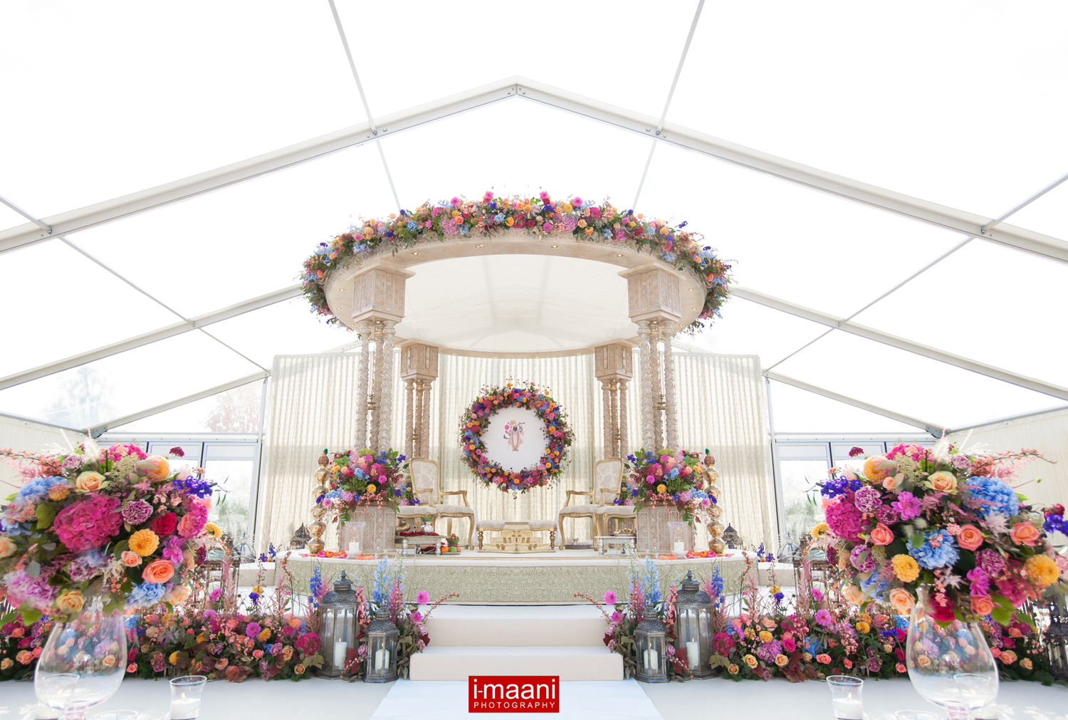 A beautiful Mandap with a border of flowers around the stage , floral Halo backdrop and a border around the perimeter of the Mandap canopy